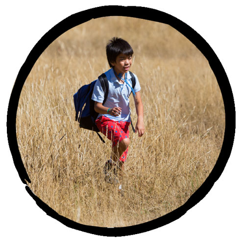 Young boy in field of dry grasses